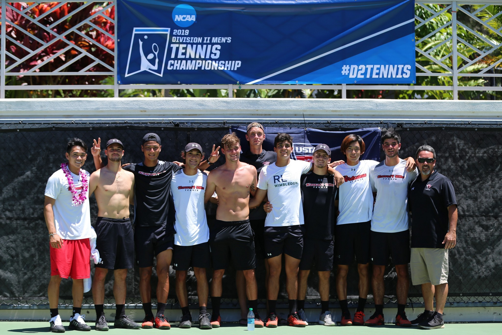 Team and coaches, 11 total, stand in front of banner that reads: NCAA 2019 Division II Men's Tennis Championship. #D2Tennis
