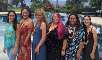 Group photo of Shantel Akau, Kailee Yoshimura, Annalise Cogan, Heather Padilla, Skye Narvaez, Ariana Dolan. Photo taken in front of pool, ocean and trees in background. Each winner wears a puakenikeni lei.