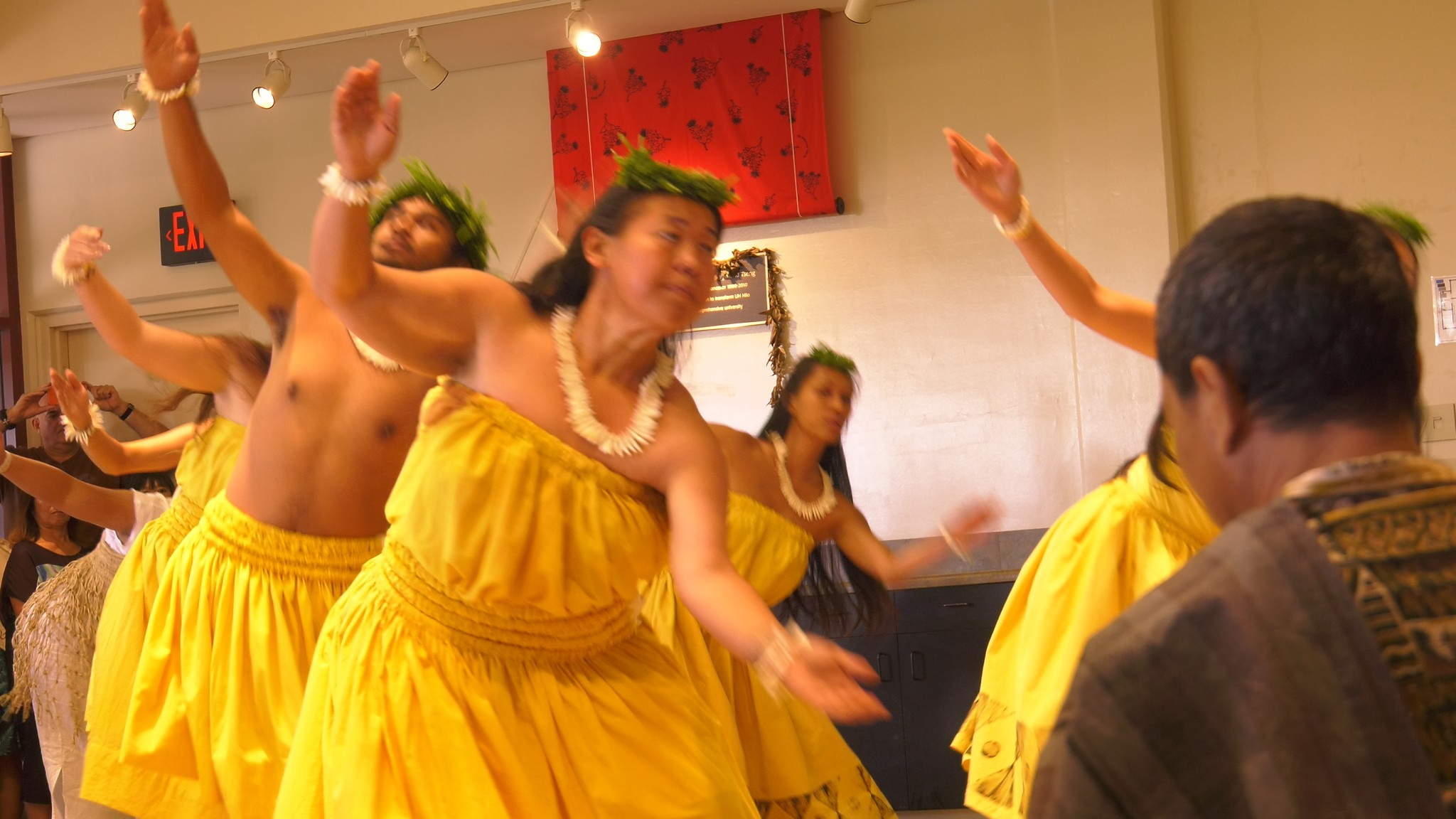 Female dancers in yellow with right arms raised.