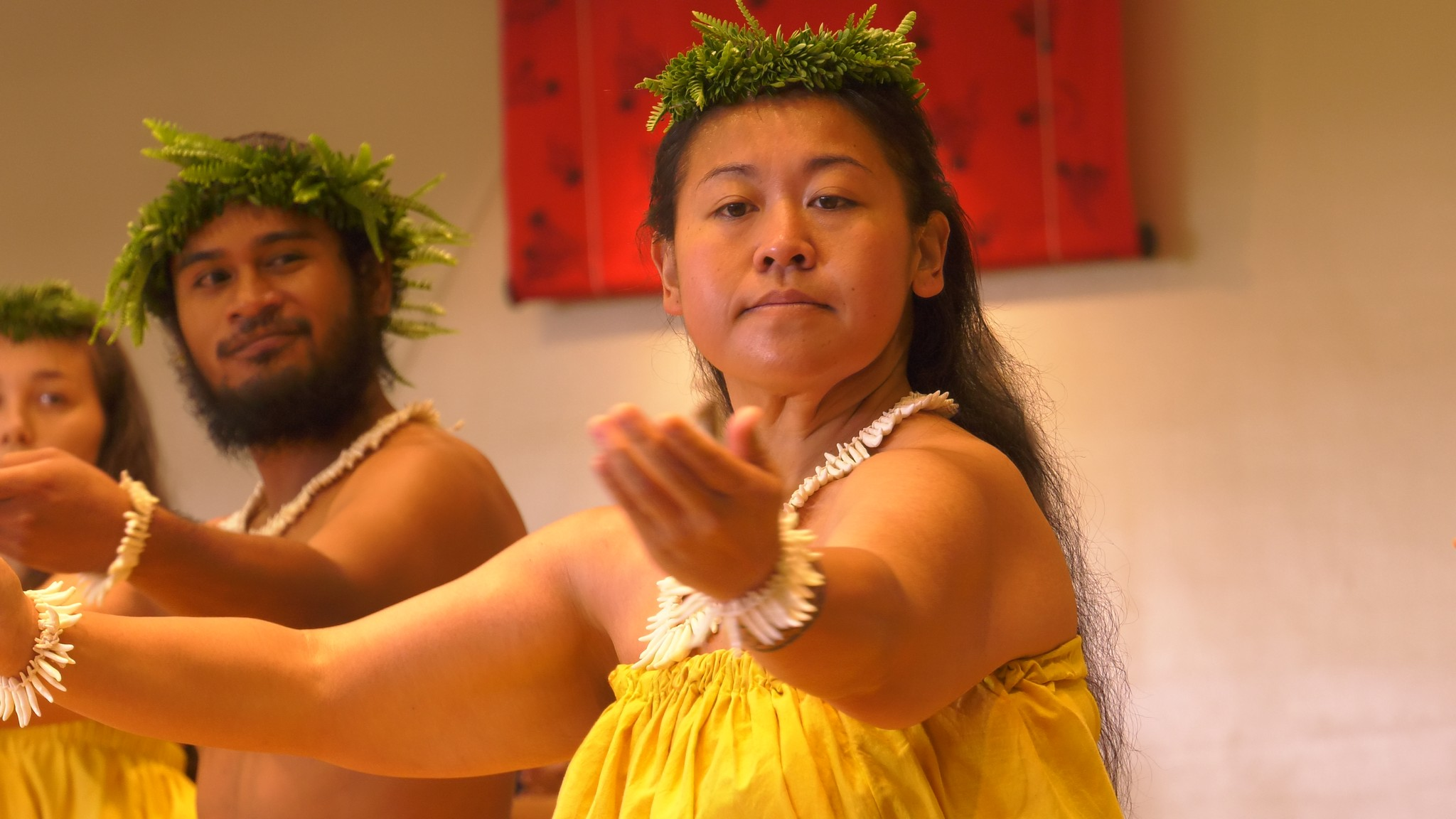 A female dancer in yellow gestures with arms out.