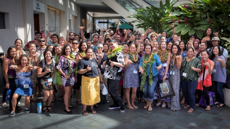 Large group of people stand for photo. a fun group, smiling and throwing the shaka.