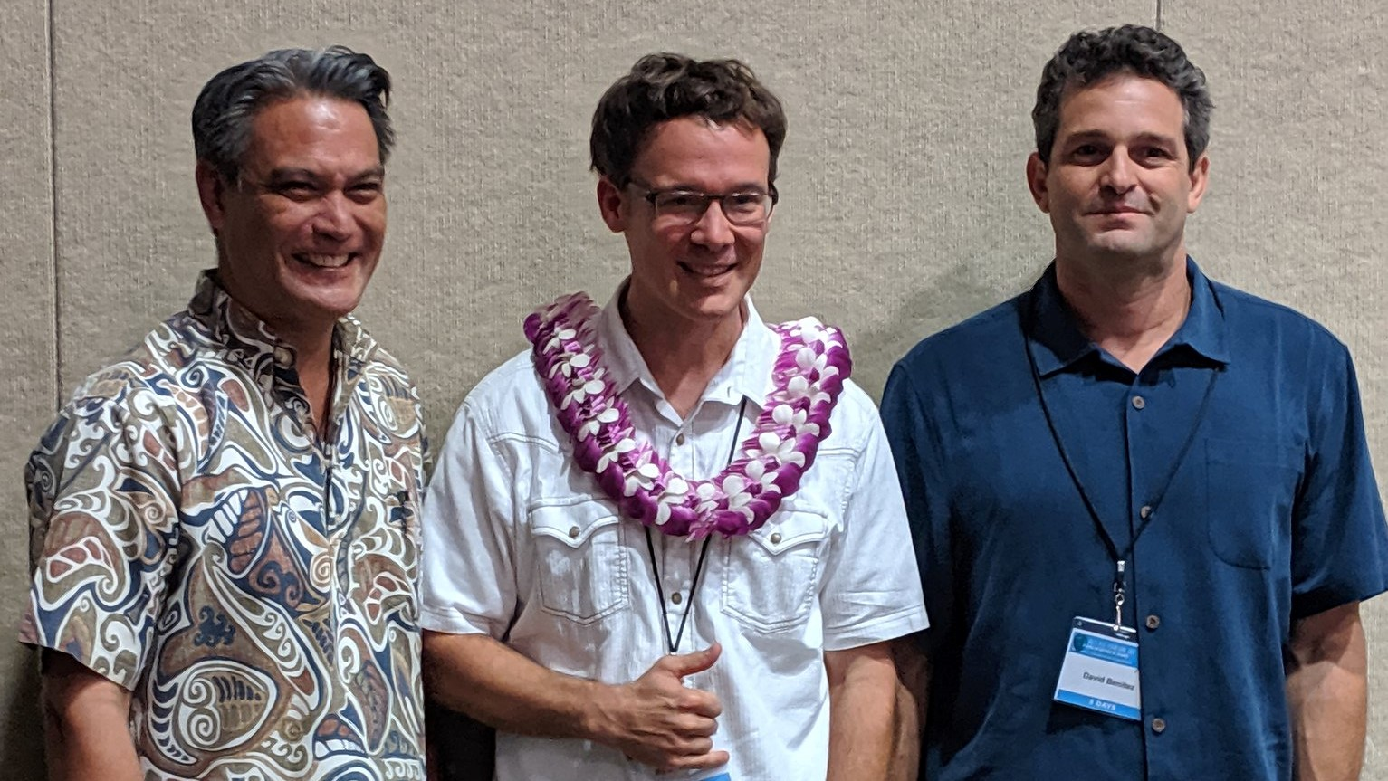 Ryan Perroy stands with presenters of award. He wears a lei.