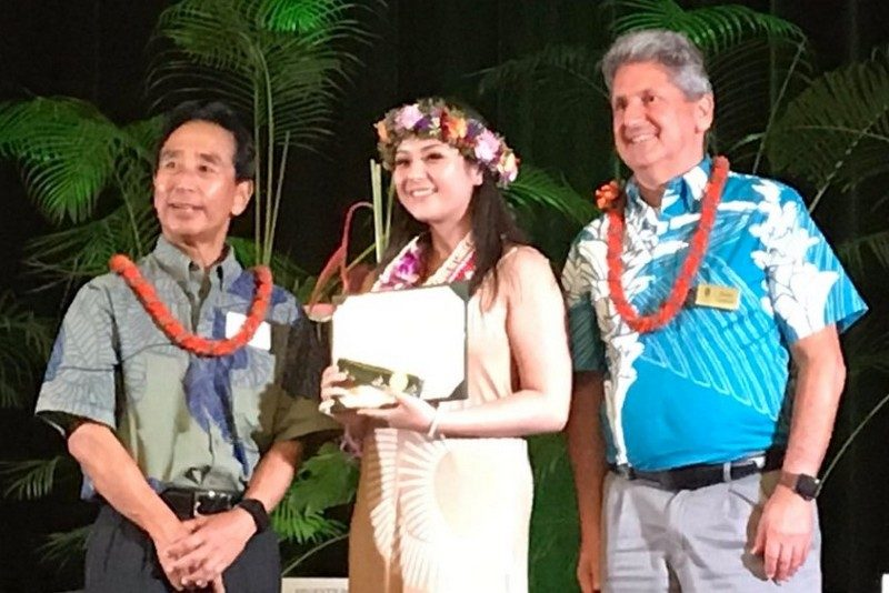 Benjamin Asa Kudo, Zoi Nakamura and David Lassner on stage to recognize Zoi's win. She holds certificate and wears a head lei.