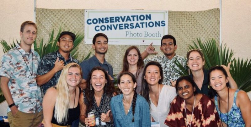 Group photo of the students with a banner behind them with words: CONSERVATION CONVERSATIONS Photo Booth. Lauhala mat as backdrop. A couple of the students are showing the shaka.