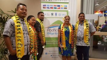 Group of five students stand for photo wearing yellow sashes and flower garlands. Behind them is a poster with the words: Pacific Ridge to Reef.