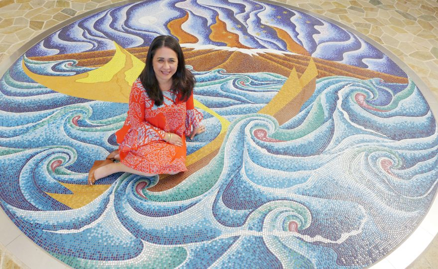 Ka'iu sits in the middle of mosaic which depicts voyaging canoes in swirling waves, with stars above.