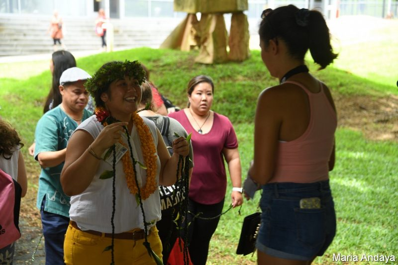 Young woman in head lei, smiling, about to give student a ti leaf lei.