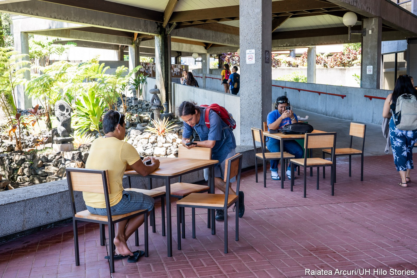 Students at beautiful wooden tables on the Library Lanai, with gardens in the background.
