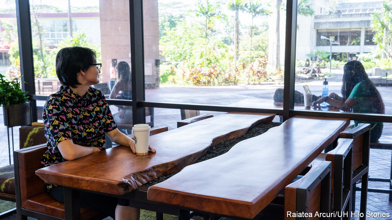 Student sits at table made of wood shaped like flowing wateer, looking out window to lanai and gardens.