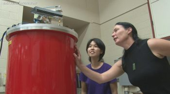 Two women stand next to large red barrel-shaped instrument.