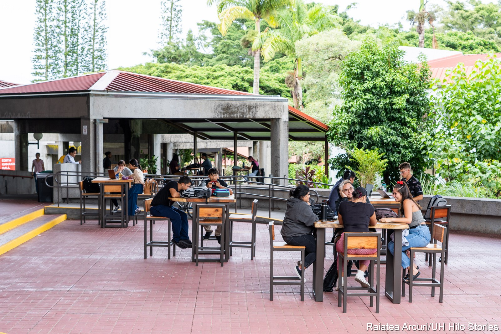 Students at tables on open lanai, greenery and trees in background.