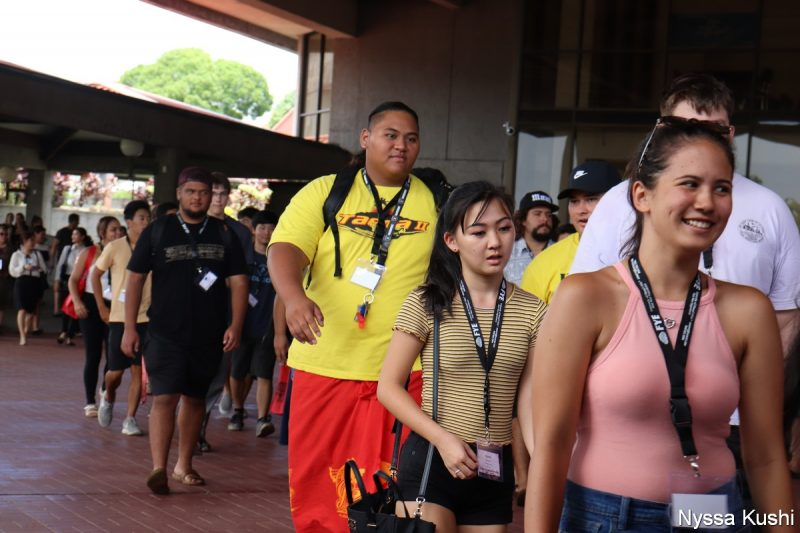 Close up of tall young man with bright yellow t-shirt walking across Library Lanai.
