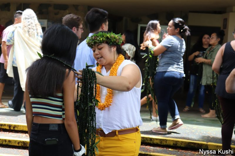 Young woman in head lei give ti leaf lei to female student,