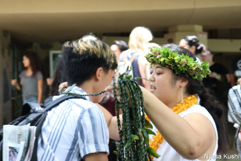 Young woman in head lei gives young man a ti leaf lei.