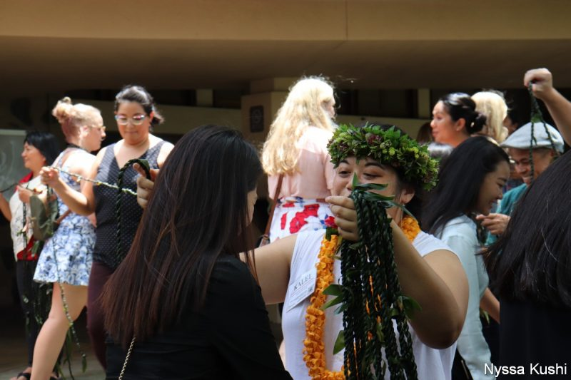 Young woman in head lei presents young womn with long black hair with ti leaf lei.