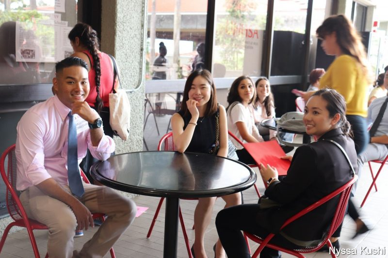 Four students sit at a cafe table near the plaza.