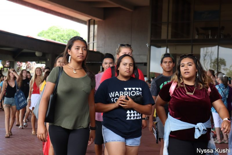 Three students, one wearing t-shirt with the word WARRIORS.
