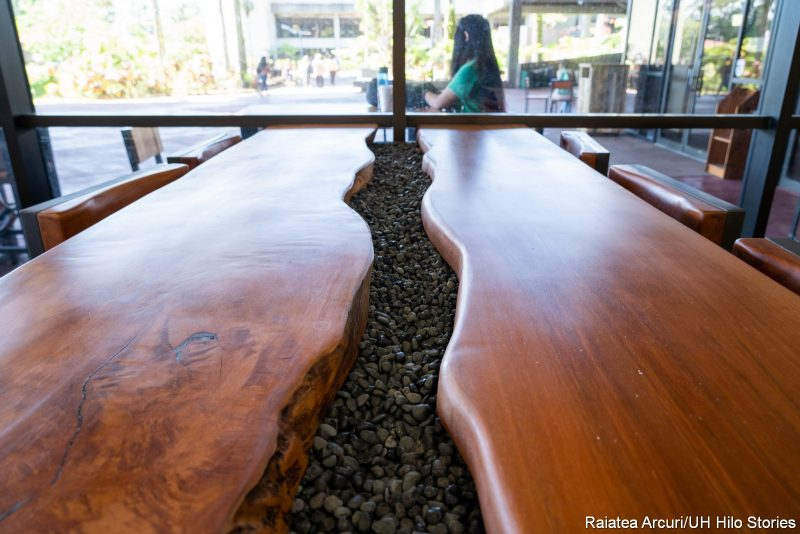 Close up of the River Table made of dark wood with a wavey strip of rocks at the center.