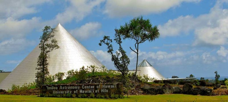 'Imiloa Astronomy Center with its three cones shaped buildings, signage in lava wall, surrounded by gardens.