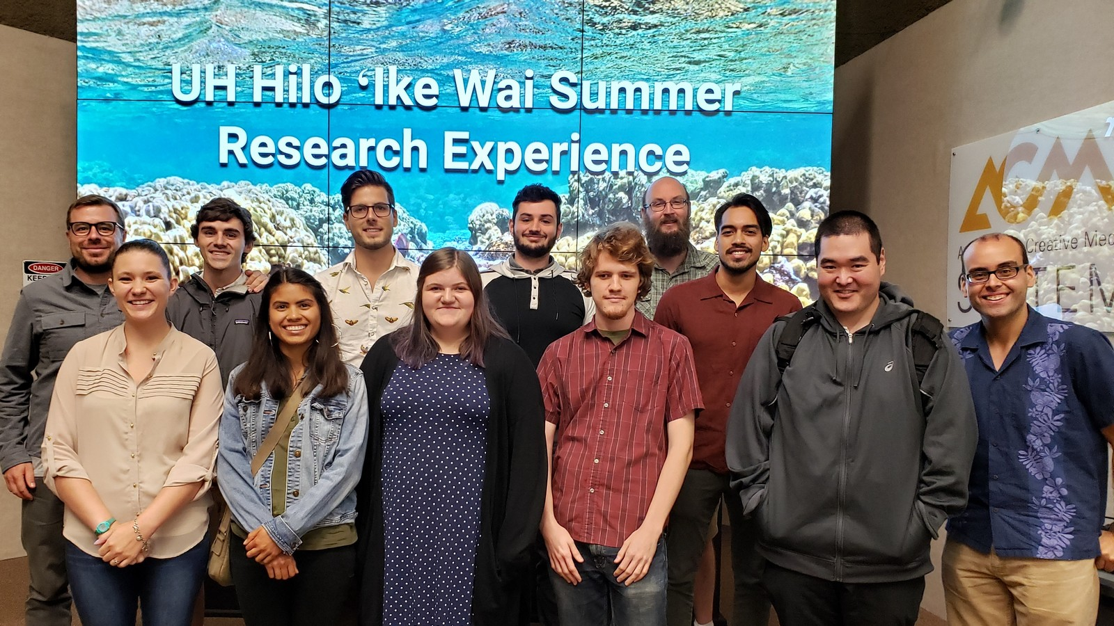 Group photo of class in front of PowerPoint slide with image of underwater coral reef and the words: UH Hilo 'Ike Wai Summer Research Experience.