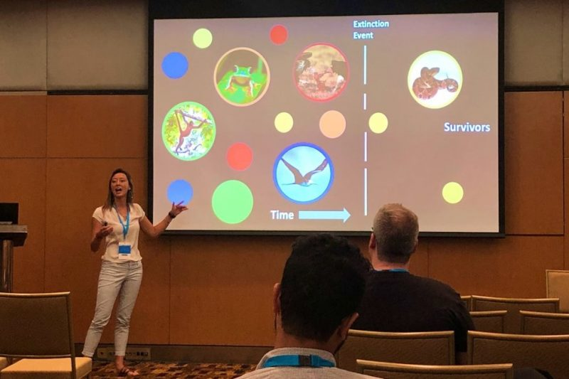 """Maya Munstermann giving a PowerPoint presentation. On the slide is a graphic of primate, frog, bird, with """"Extinction Event"""" line and on the other side of the line, a snake."""