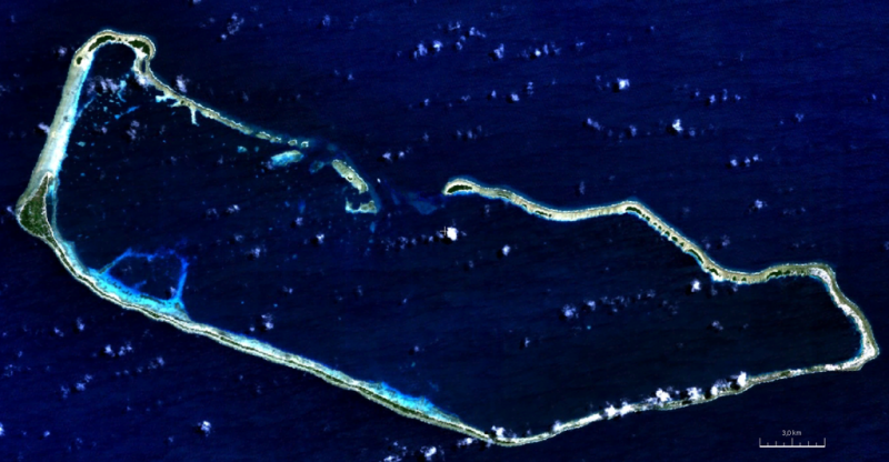 An aeiral view of atoll, a ring shaped island surrounding a lagoon.