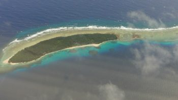 Sliver of atoll, beach on one side, reef offshore.