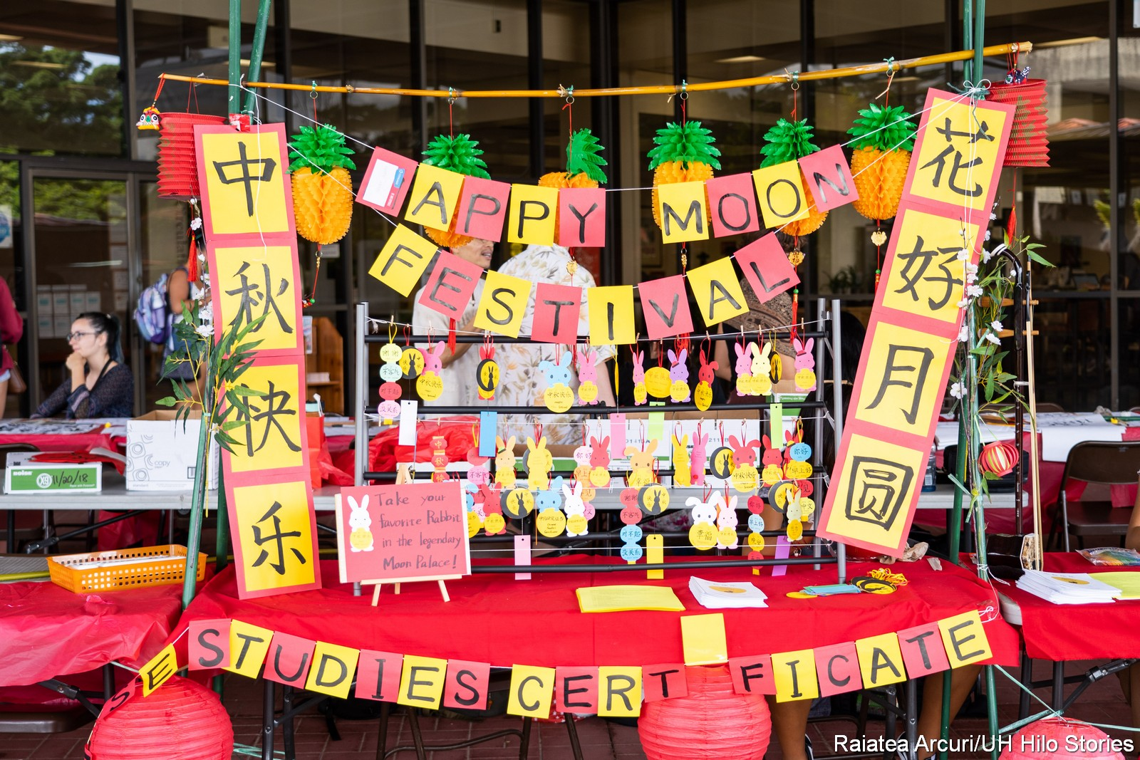 "Colorful table display with paper cut outs of the words ""Happy Moon Festival."" Also Chinese characters. And in front of table the words"" ""Chinese Studies Certificate."""