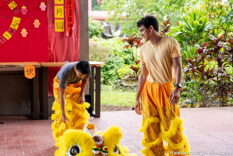 Two men putting on the lion costume.