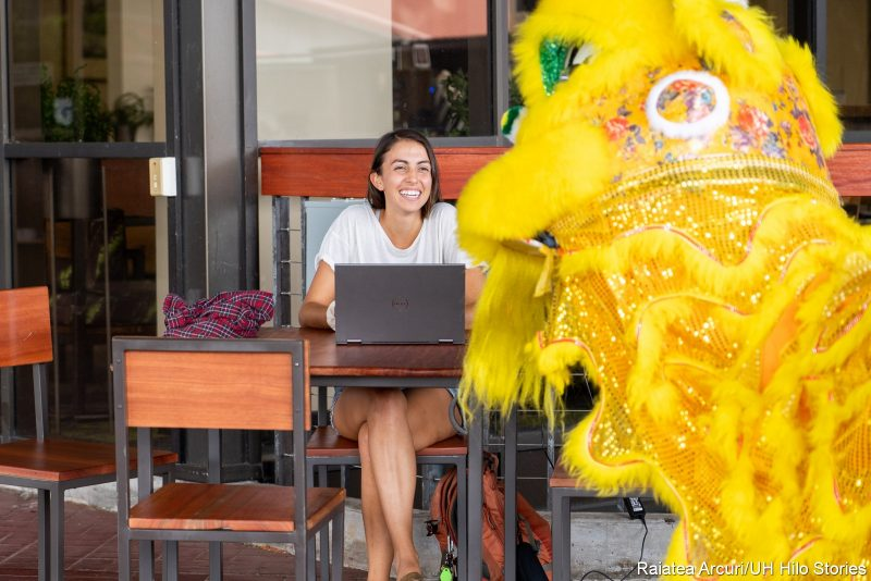 A woman seated with a laptop looks up and smiles at the lion.