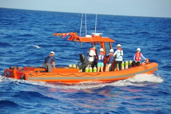 Small boat at sea with team of scientists.