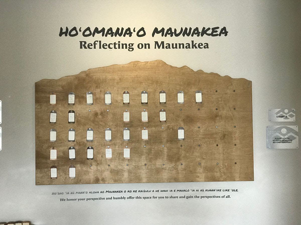 "Exhibit with area for people to post notes. Title at top: ""Hoomanao Mauankea, Reflecting on Maunakea."" At bottom, Hawaiian and translation: ""We honor your perspective and humbly offer this space for you to share and gain the perspectives of all."""