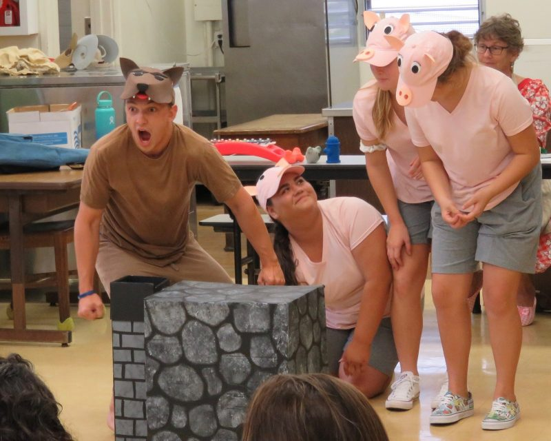 In costume, three actors as little pigs, and a wild dog grabbing a little stone house.