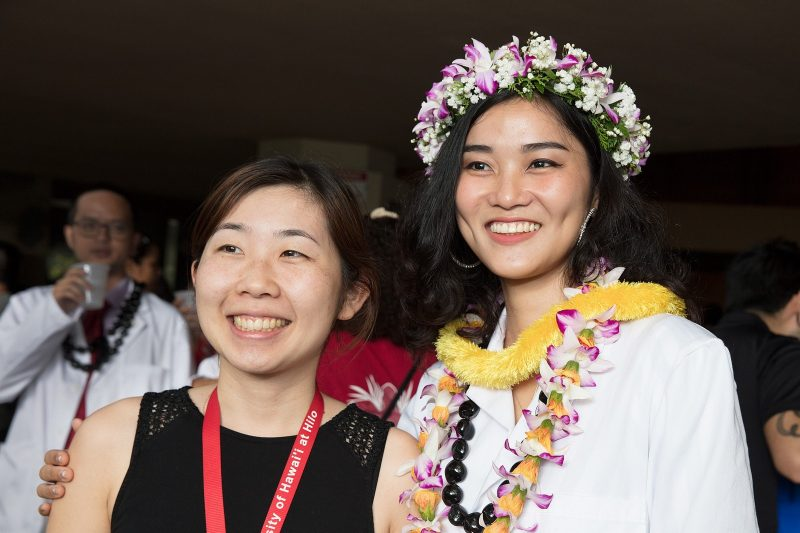 Student in white coat and head lei with well wisher.