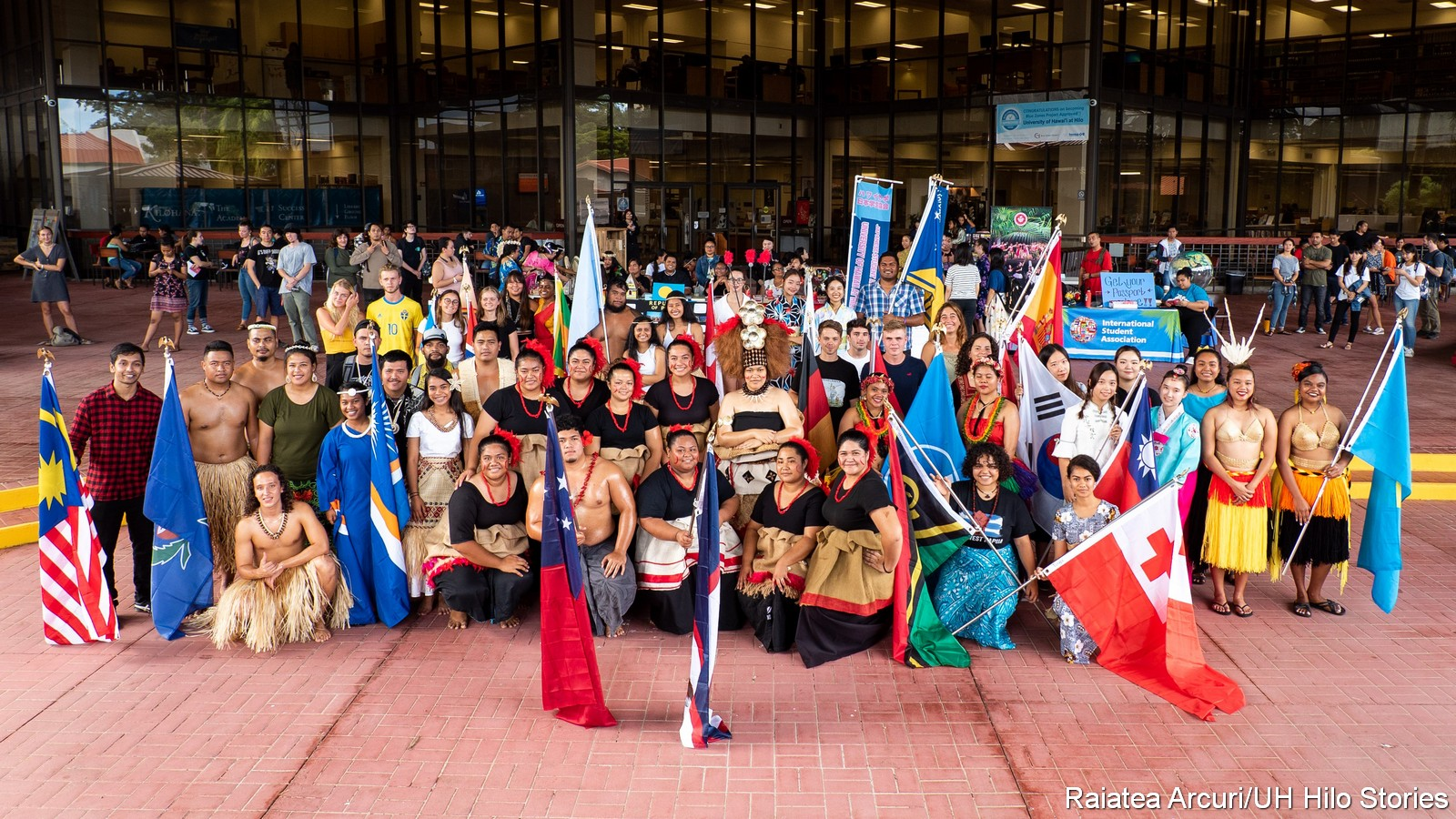 Large group of students in traditional attire of their homelands. Some hold flags from their nation. In the background in the glass facade of the library.