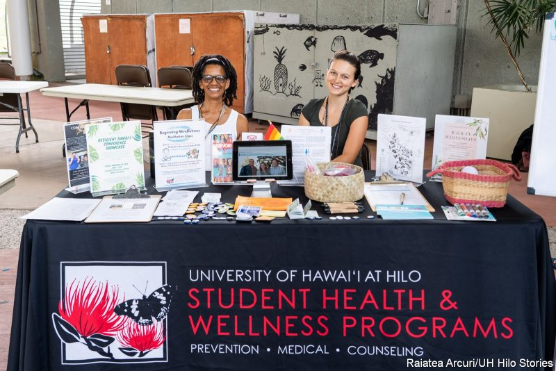 Two young woman at an informational table. Banner reads: University of Hawaii at Hilo Student Health and Wellness Programs.