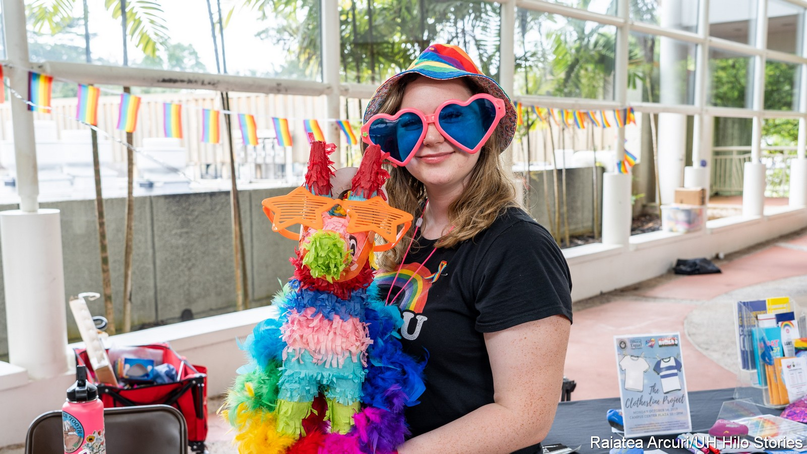 Young woman in huge sun glasses with pink framed lenses shaped like hearts. She holds a animal figure made of fringed rainbow colored paper. Her t-shirt has a rainbow on the front, and she wear a rainbow colored hat.