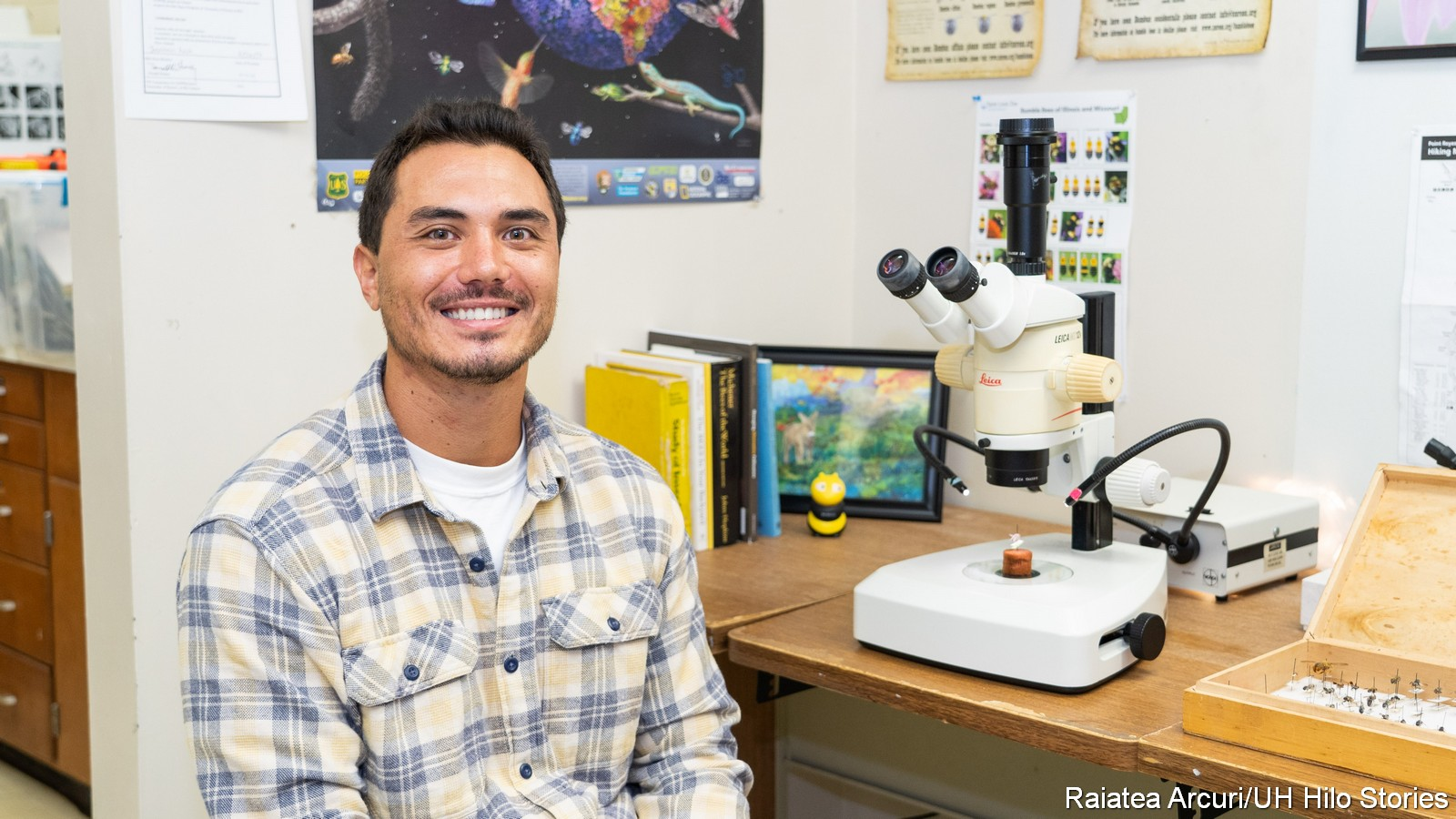 Jesse Tabor sits at desk. On desk is microscope and bee display.