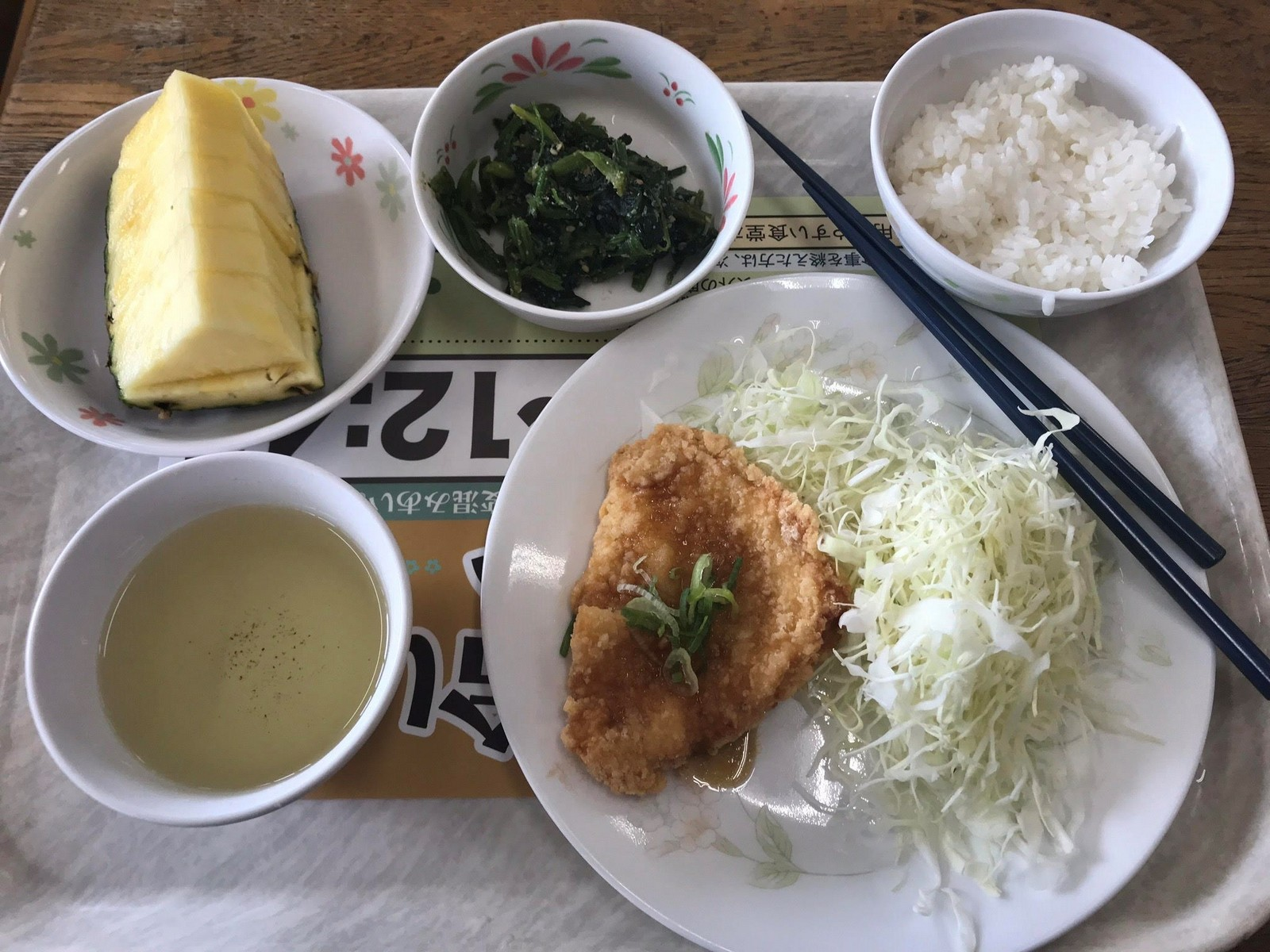 Plate of Japanese food, fruit and vegetables, rice, fried fish, chopsticks on plate.