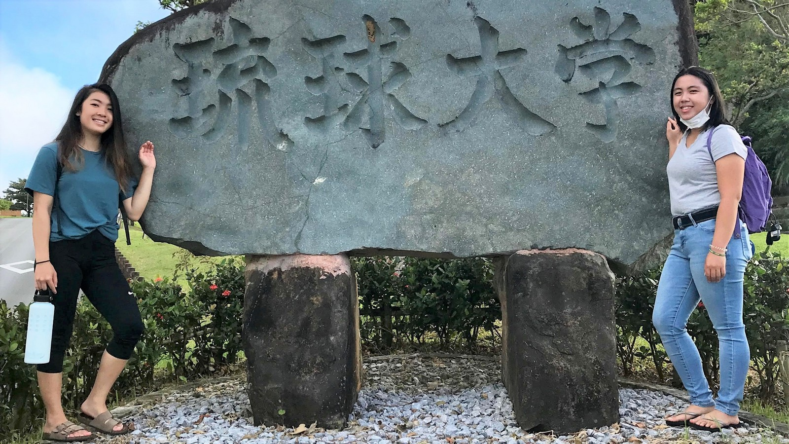 LiAnn Yamamoto stands with friend at stone carving with Japanese lettering.