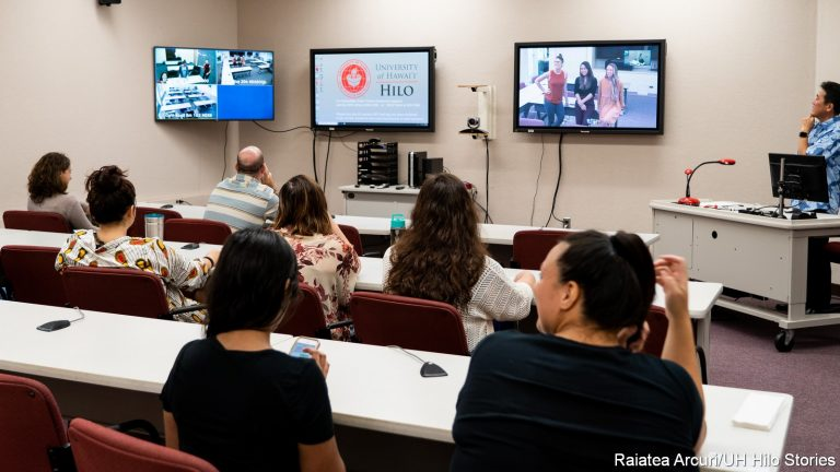 Class is interacting with classmates via telecommunications. Large screens at the front of the classroom show long distant students participating in the class.