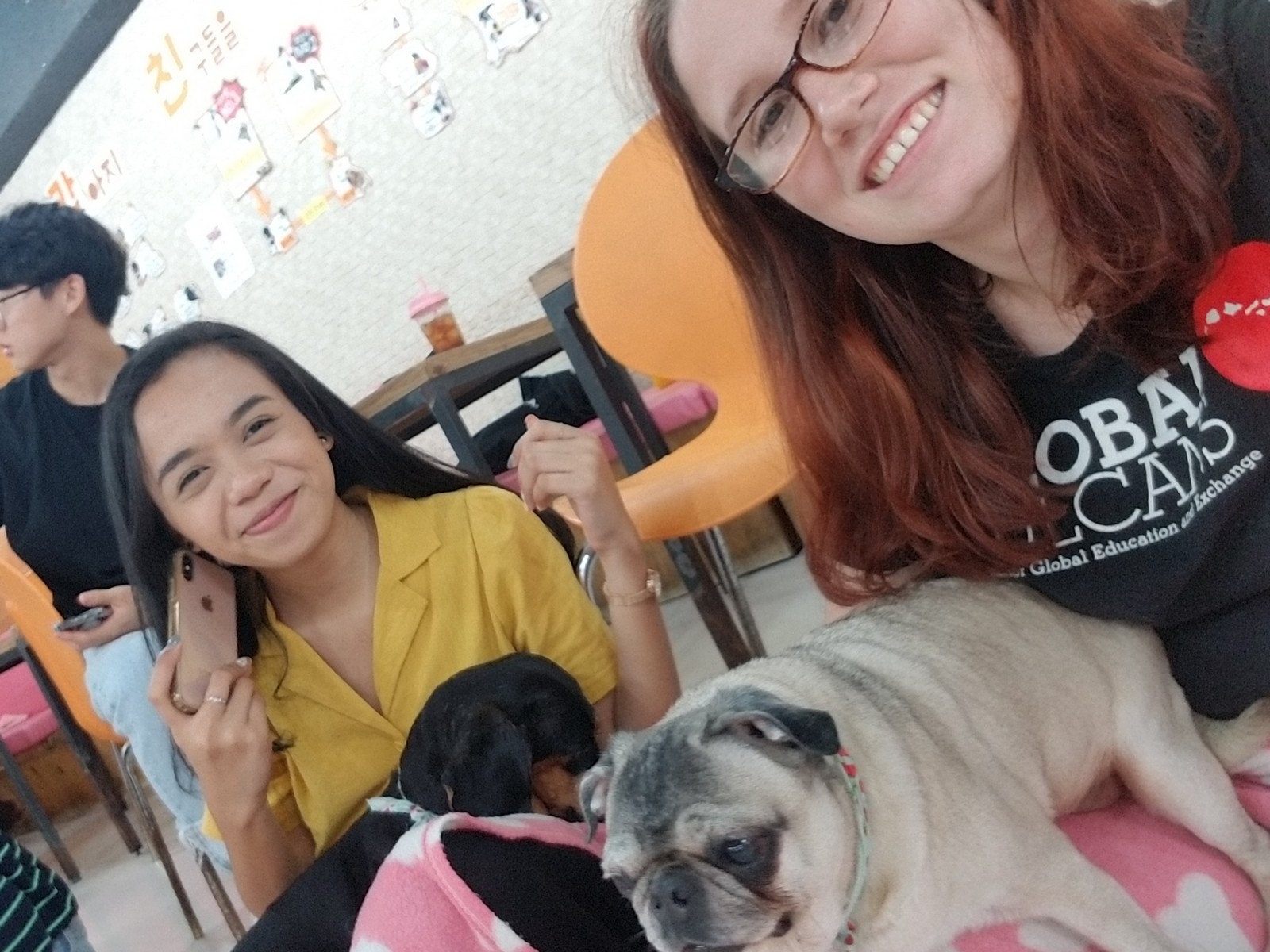 """Sienna with friend, each holding cute dog. Sienna is wearing her """"Global Vulcans"""" t-shirt."""