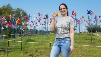 Sienna stands on lawn with hundreds of pinwheels on tall stakes in the background. She's flashing the peace sign.