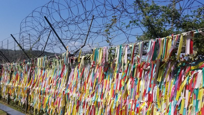 Thousands of ribbons on fence. Above are coils of barbed wire to stop people from climbing over.