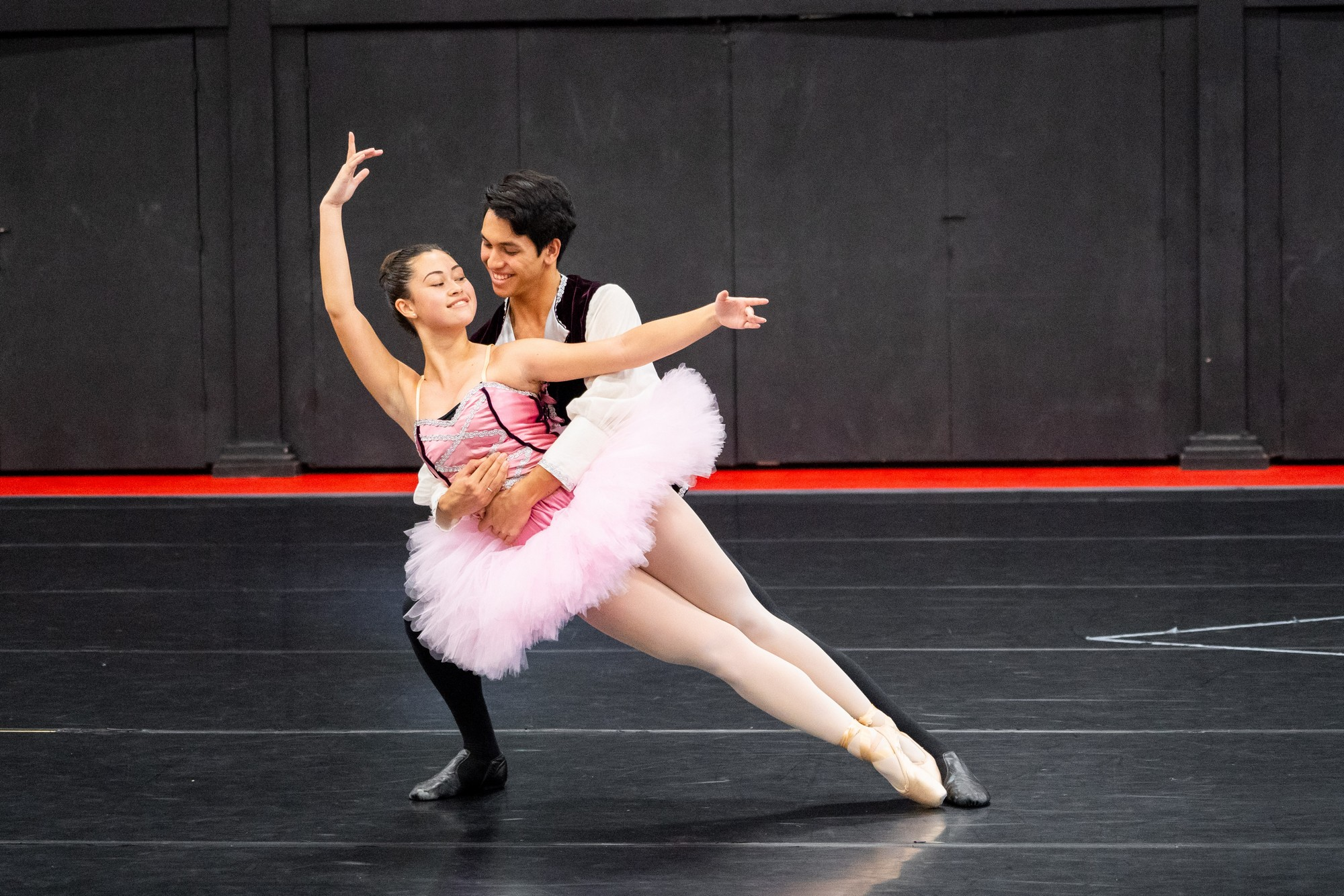 Couple in ballet pose, she in pink tutu, he in royal costume.