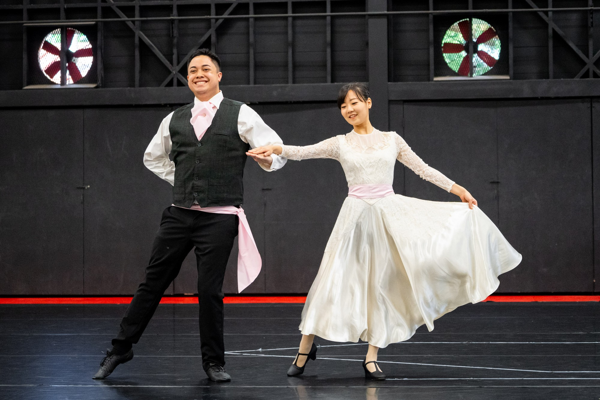 Couple in formal wear in ballet pose with right feet pointed to the right.