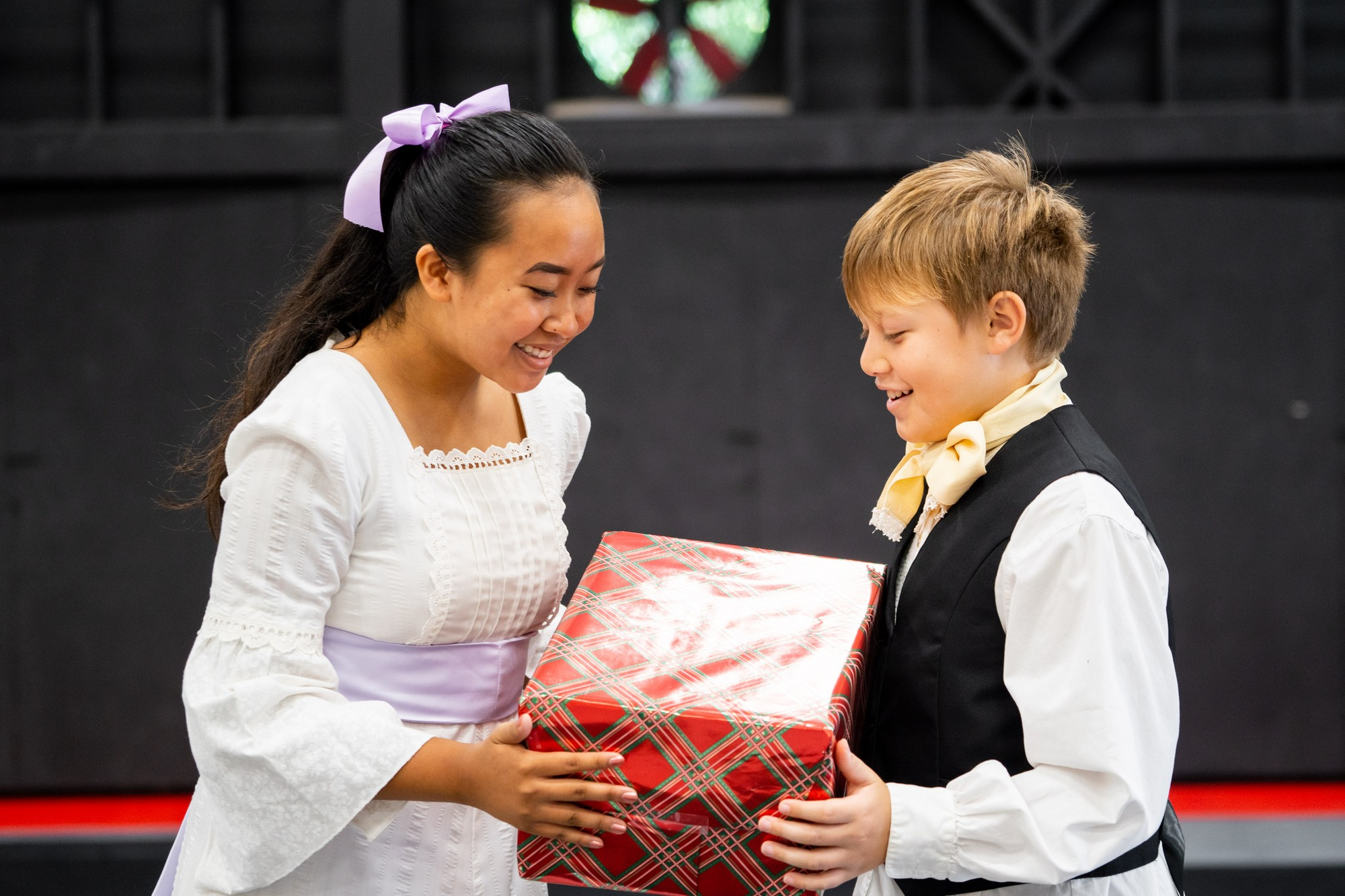 Young girl gives boy a wrapped gift.