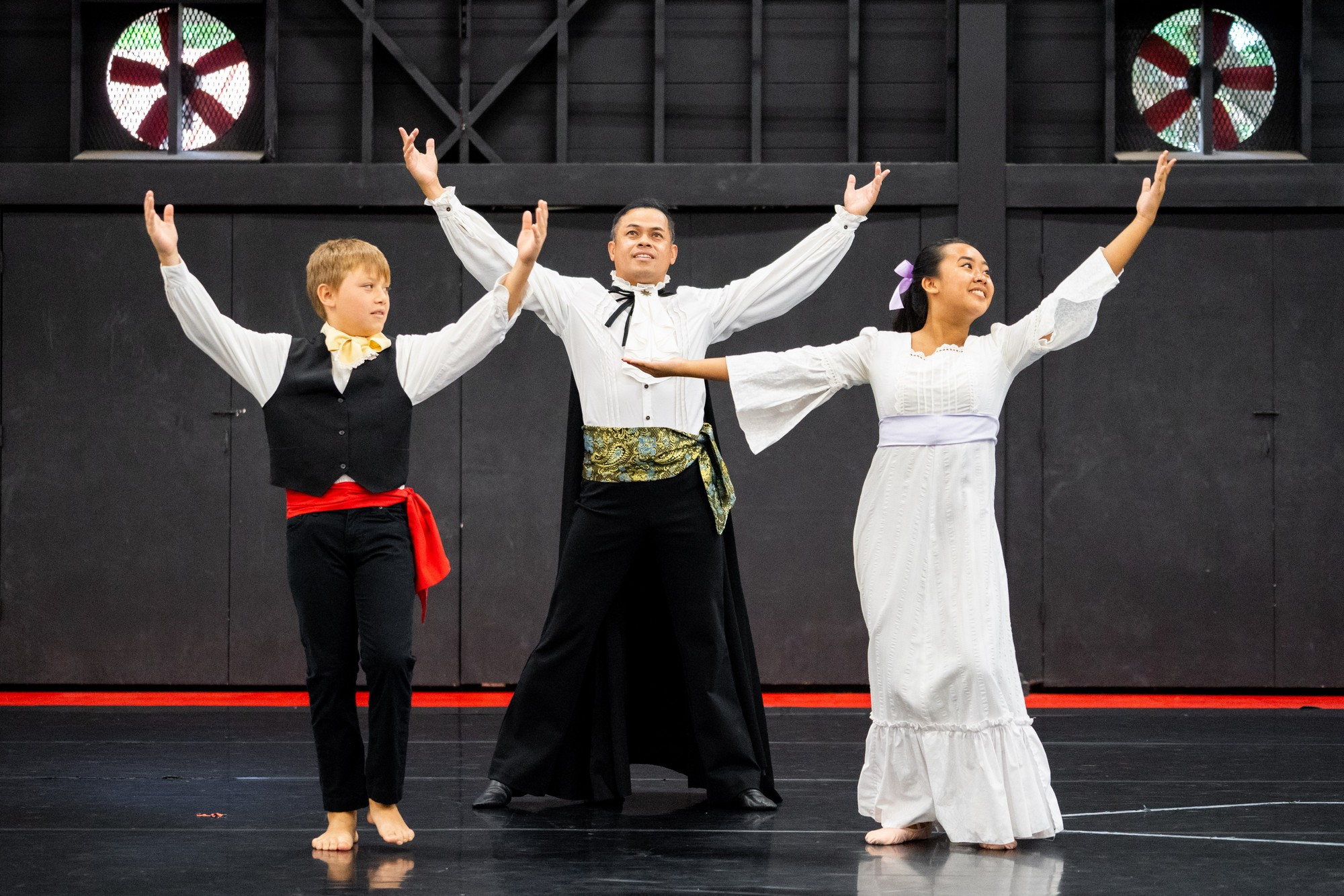 Micah Polloi, Norman Arancon, and Lydia Kamakaʻeha, in costume, with arms raised high. Norman wear dramatic sash and cape.