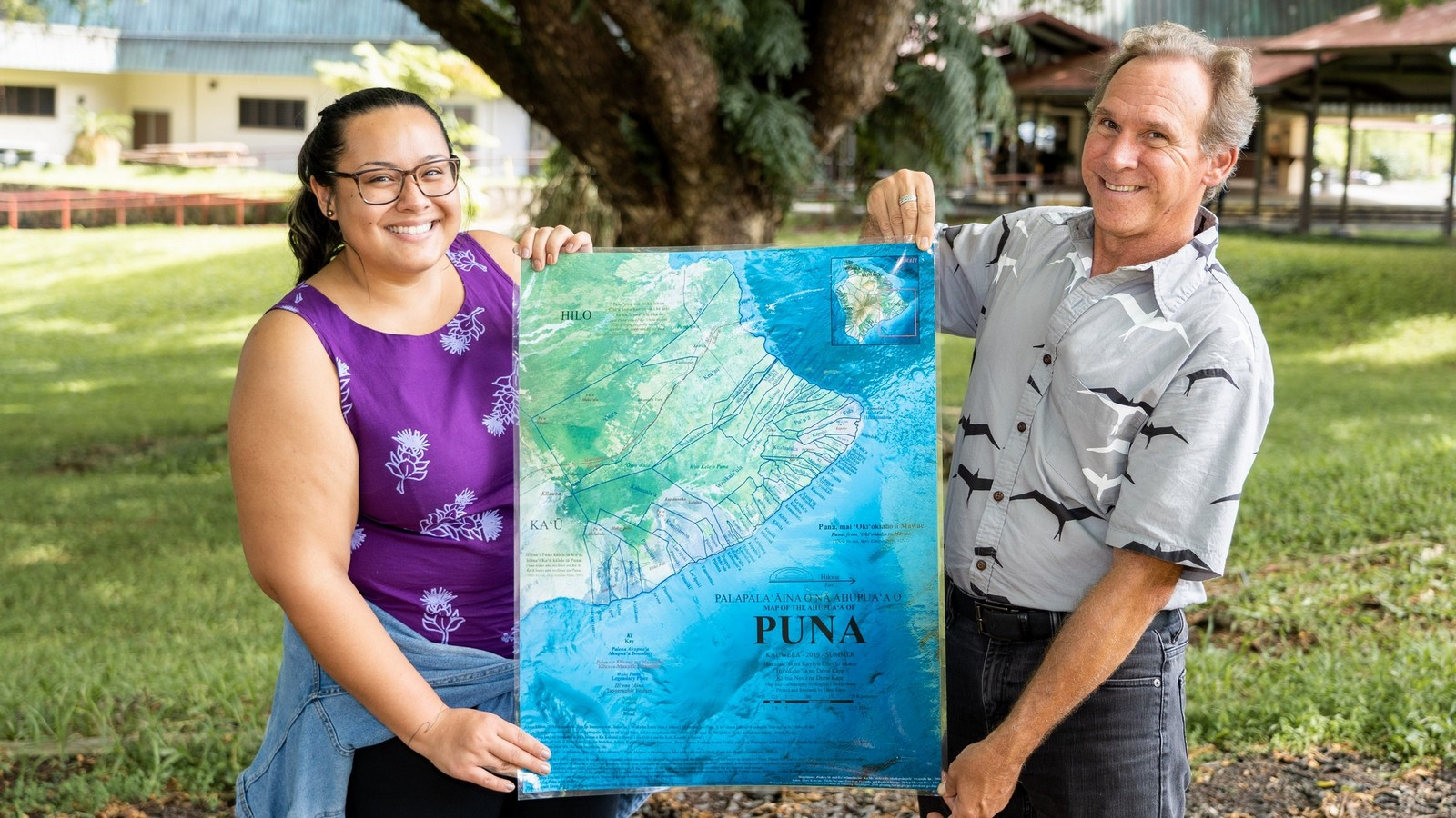 "Kaylyn Ells-Ho'okano and Drew Kapp hold up a large copy of the map they created: blue ocean surrounds the south east tip of the island. Map is labeled ""PUNA."" Place names and other details on map are too small to read."
