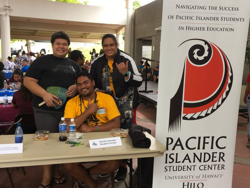 """Three students at informational table, """"Pacific Islander Student Center."""""""